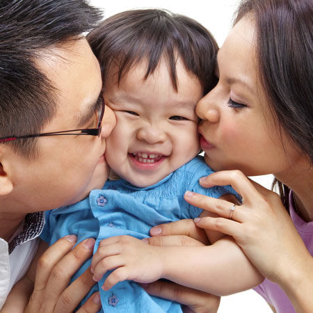 Couple Kissing Smiling Child
